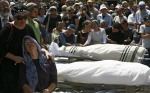 Mourners gather around the bodies during funeral in the West Bank Jewish settlement nearHebron
