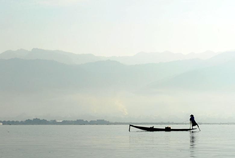 Poranne mgły i samotna łódź na jeziorze Inle