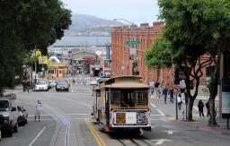 Tramwaje jeżdzą po ulicach SF od XIX stulecia. W tle, na horyzoncie, słynne więzienie Alcatraz.